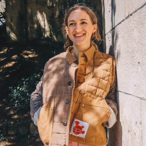 Martha Rice wears the brown quilted jacket made from upcycled materials. This circular design features vintage remnants. Unisex and oversized. photography by Maisie Walker in Bath, Sydney Gardens.