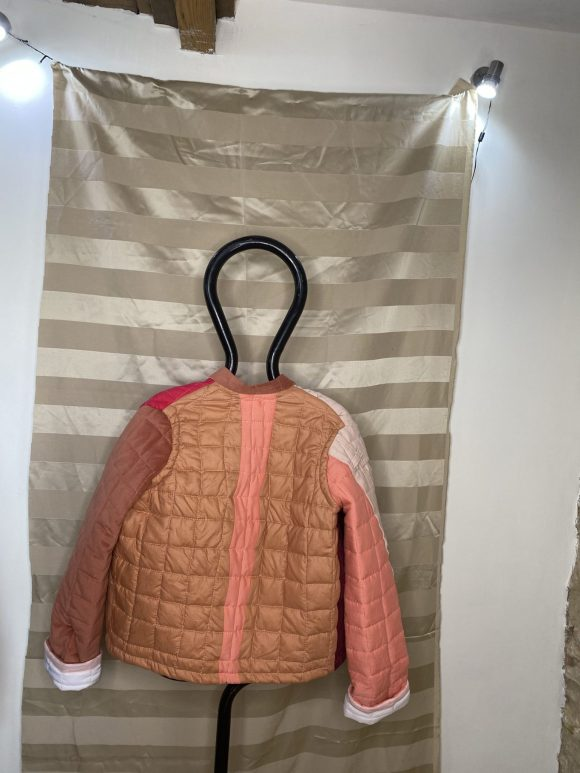 Back of pink quilted jacket made from upcycled remnant materials. Unisex and oversized jacket.