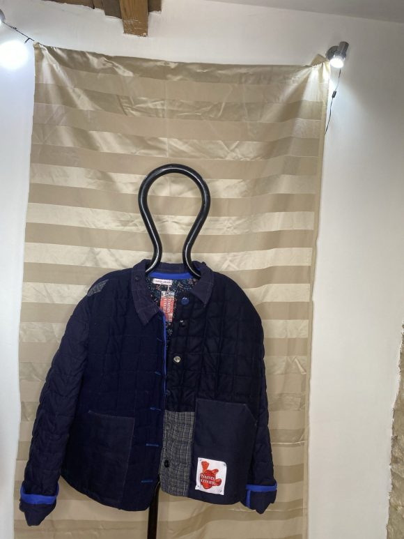 Front photo of the blue quilted jacket made from wool remnants on stand I'm the silk mill frome
