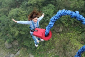 girl bungee jumping off of a bridge with forrest in the background