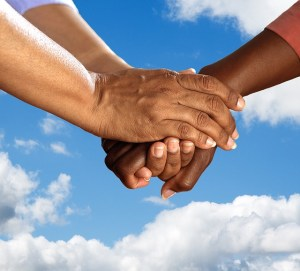 Finding yourself starts with helping others. This picture is three hands embracing with sky and clouds in the background.