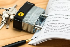 A padlock with the keys in it connected to a Legal Disclaimer and Terms of Use Agreement. A pen sits at the bottom of forms. They are laying on a wood table.