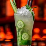 A cucumber mojito drink in a tall glass with cucumber slices, rum, mint, club soda, lime juice, and simple syrup. Glass sitting on table with lighted background. Drink garnished with cucumber wedge and a sprig of mint.
