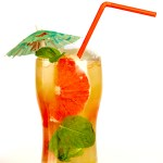 A grapefruit mojito drink with grapefruit juice, mint, lime juice, sugar, rum, and sparkling water. Garnished with slice of grapefruit and a sprig of mint. Served in a tall glass with red straw.