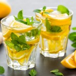 two short glasses with club soda, lemons, basil, and honey. Garished with lemon slices and a sprig of mint.