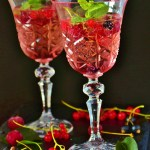 a gobblet glass of Berry Blend Mojito with strawberries, raspberries, and blueberries mixed with lime, mint, simple syrup and ckub soda.