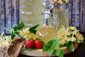 Simple Syrup in a glass bottle with pitcher and a jug full of it. Sitting on a wooden table with strawberries and white flowers and green leaves around the containers.