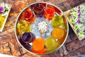 a round metal tray with short glasses of different flavors or syrup. Purple, orange,yellow,, and blue colored. A glass with flowers inside is in the middle of the tray.