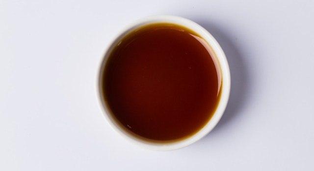A cup of peach syrup in a white coffee cup sitting on a white table.
