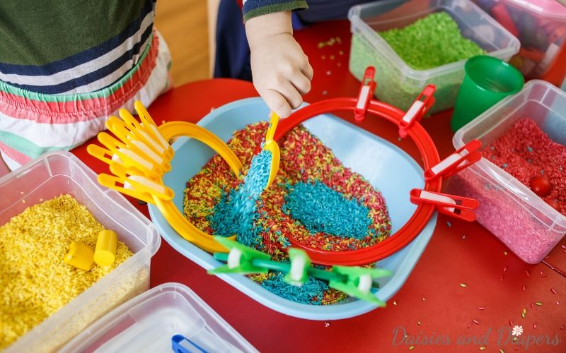 toddlers playing with rainbow rice