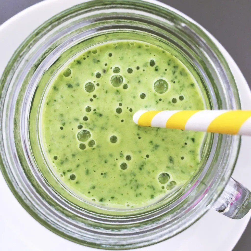 close up view inside the top of a glass of green smoothie with stripy yellow and white paper straw