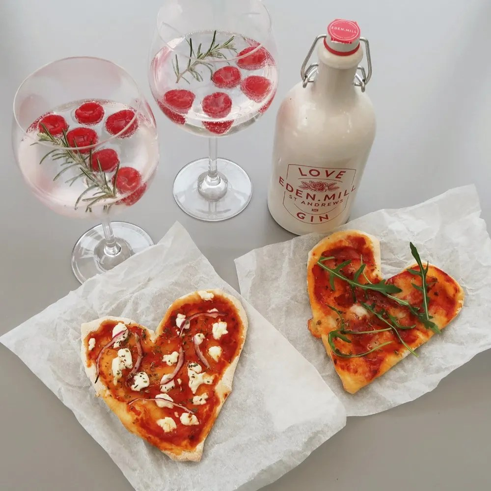 Heart shaped homemade pizza topped with goats cheese and red onions, alongside Eden Mills gin and two gin cocktails garnished with raspberries and fresh rosemary
