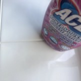 white bathroom tiles with freshly cleaned grout, bottle of ACE Power Mousse stood on the tiles