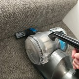 VAX Blade 32V cordless vacuum cleaner with the stairs tool being used to vacuum the stairs - grey carpet