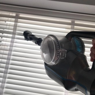 VAX Blade cordless vacuum being used with the 'up top' tool to clean venetian blinds