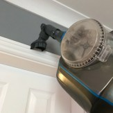 VAX Blade cordless vacuum being used with the 'up top' tool to clean the top of door frames