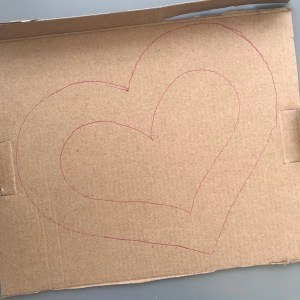 heart shape drawn onto cardboard in pink biro