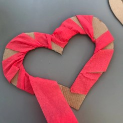 red crepe paper streamer wrapped around a cardboard heart