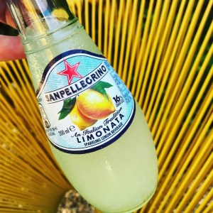 bottle of sanpellegrino limonata held in front of yellow wire garden chair