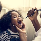Little girl having her teeth checked by dentist in lake forest