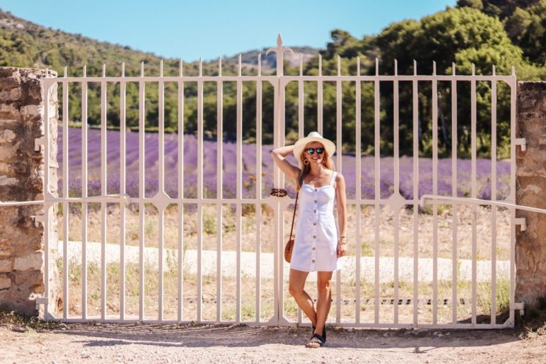 standing by lavender field with white gate