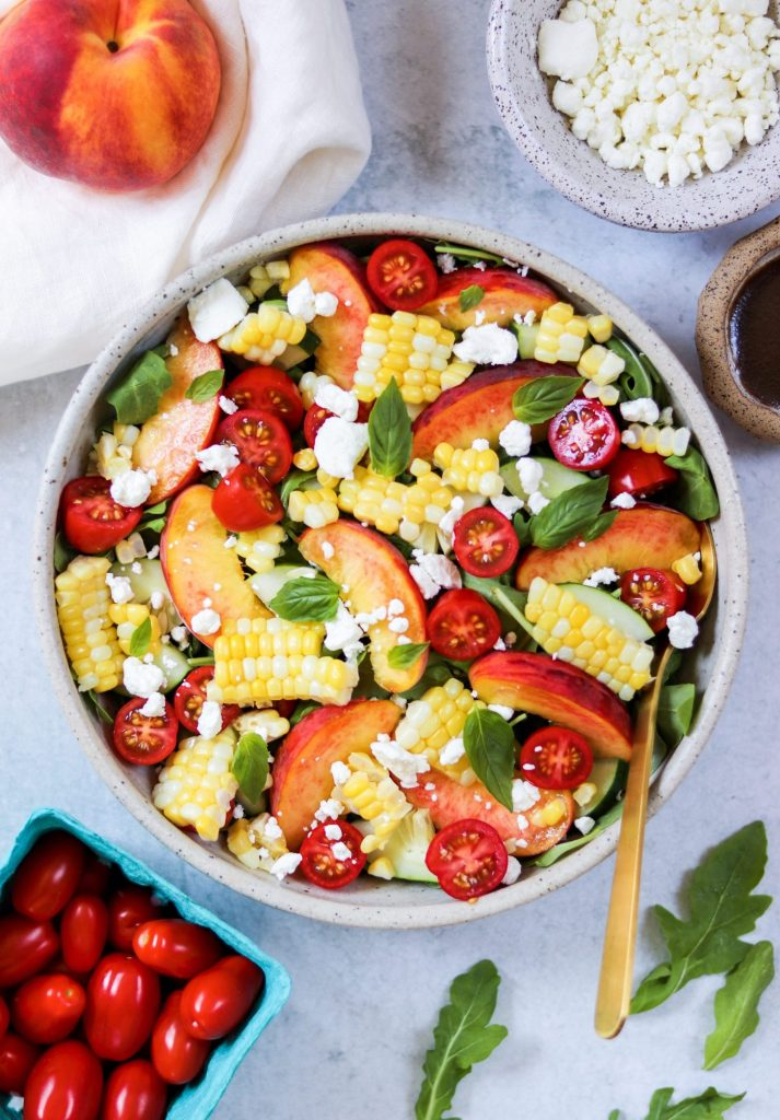 Peach salad bowl surrounded by ingredients - Daisybeet