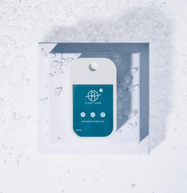 Desinfektionsmittel 'PLANET HOME to go' für Unterwegs in einem handlichen Designsprayer auf einem Sockel liegend