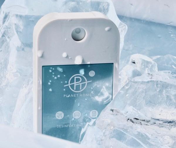 Desinfektionsmittel 'PLANET HOME to go' für Unterwegs in einem handlichen Designsprayer zwischen Eiswürfeln