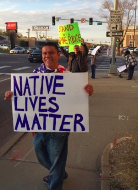 The flag stands for Native lives, too. Protesting racism on Minnesota Avenue, Sioux Falls, SD, 2017.10.13. Photo by Carrie Johnson.