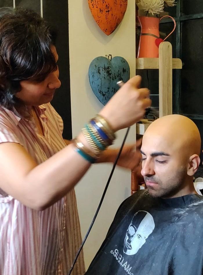 Preetisheel Singh working on Ayushmann Khurrana's look on the sets of Bala. Pic 1.