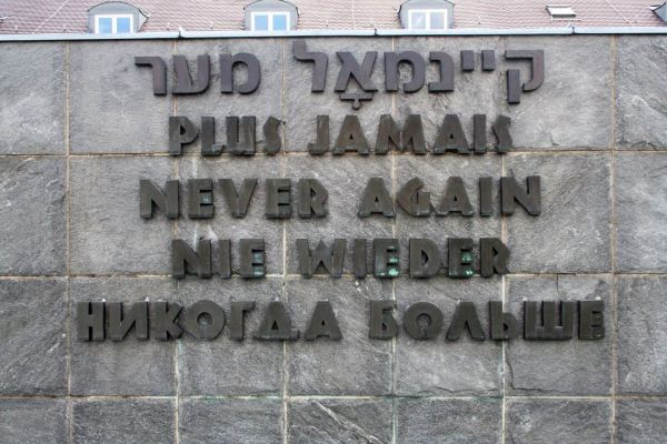 "Sign reads ""Never again"" in five languages: Hebrew, French, English, German, and Russian."