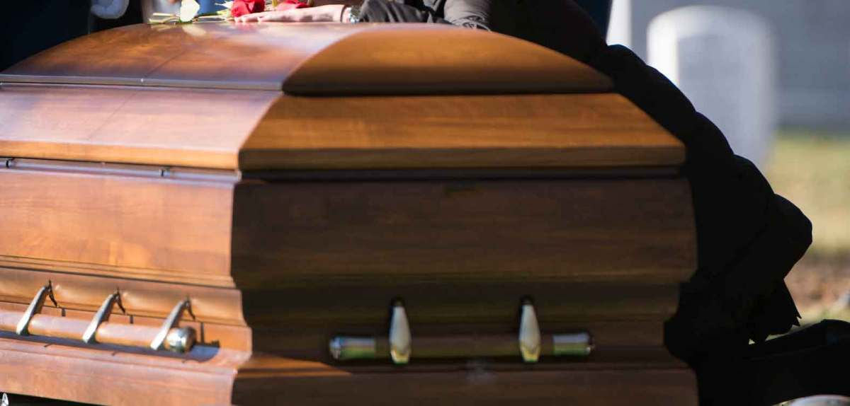 Woman leaning on casket at funeral. Wrongful death attorney.