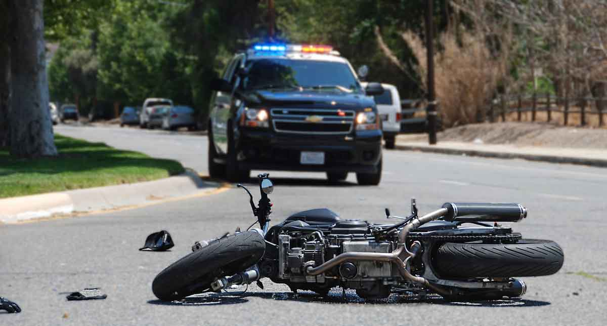 Motorcycle on roadway after collision with police on the scene. Motorcycle accident law firm.