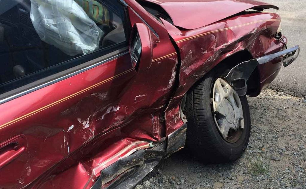 Damage to right side of maroon vehicle. Total loss value of vehicle