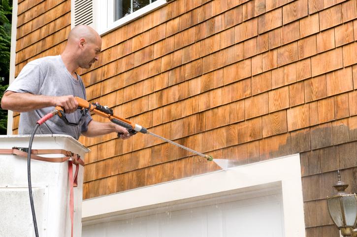 close up of man power washing exterior shingles
