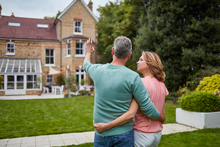 Mature couple standing in front of house