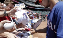 ARLINGTON, TX - MAY 18: Yu Darvish #11 of the Texas Rangers autographs baseballs for fans before a baseball game against the Toronto Blue Jays at Globe Life Park on May 18, 2014 in Arlington, Texas. Texas won 6-2. (Photo by Brandon Wade/Getty Images)