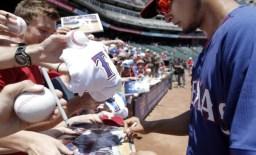 ARLINGTON, TX - MAY 18: Yu Darvish #11 of the Texas Rangers autographs baseballs for fans before a baseball game against the Toronto Blue Jays at Globe Life Park on May 18, 2014 in Arlington, Texas. Texas won 6-2. (Photo by Brandon Wade/Getty Images)