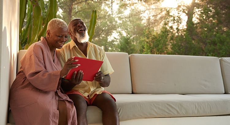 Older couple laugh with a digital tablet