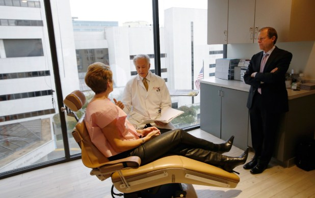 Laura Miller, former Dallas mayor, and her husband, Steve Wolens, talked with Dr. William M. Carpenter about her implants in his office in Dallas on Tuesday. (David Woo/The Dallas Morning News)