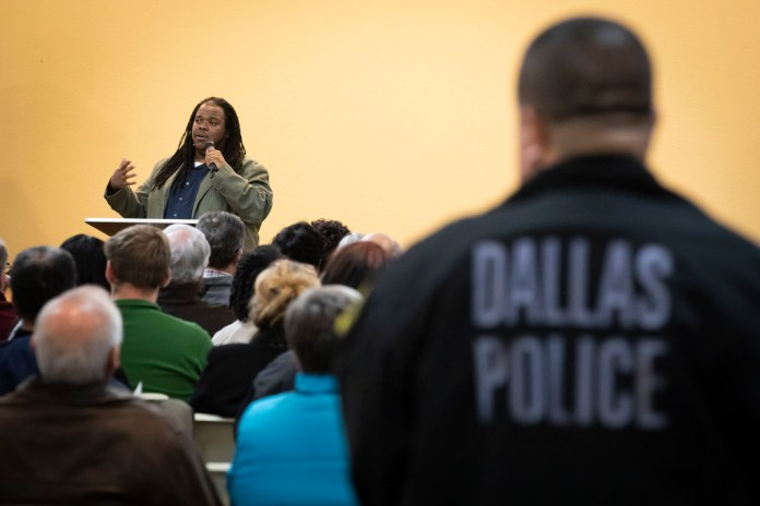 A Dallas Police officer listens as Walter