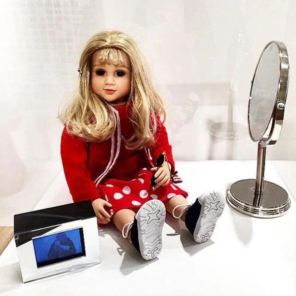 Lynn Hershman Leeson, CybeRoberta. Custom-made doll, clothing, glasses, webcam, surveillance camera, mirror, original programming and telerobotic head rotating system. 1996.