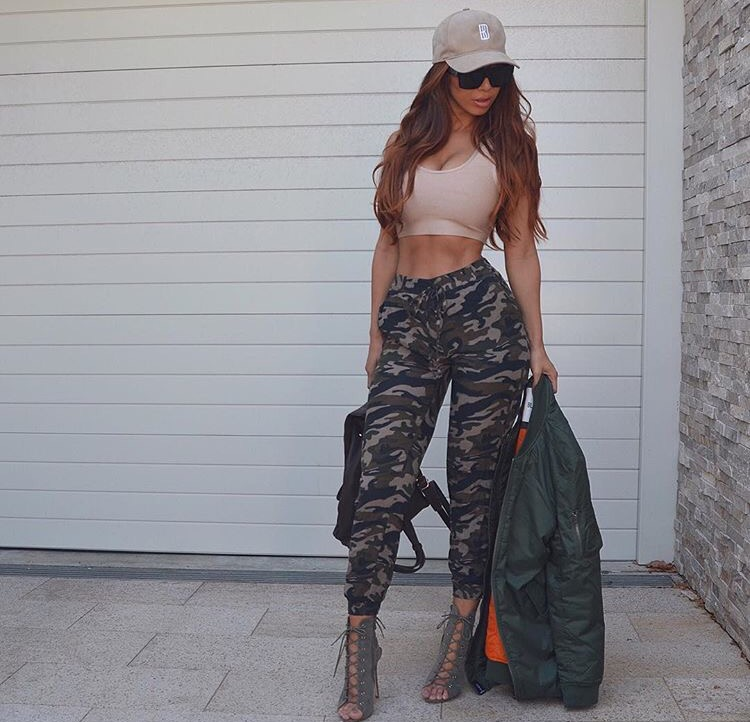 itslydboss in camoflauge pants and a crop top with green lace up open toe booties and a baseball cap and sunglasses and green bomber jacket