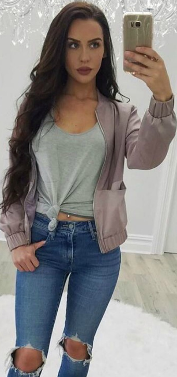 carlibybel wearing a purple bomber jacket with a grey tshirt and ripped blue jeans