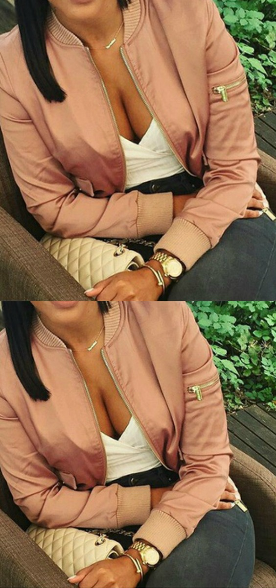 a women wearing a blush satin bomber jacket with gray jeans and a cream nude chanel bag