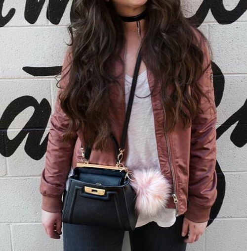 A teenager wearing a pink satin bomber jacket with jeans and a black choker necklace with leggings