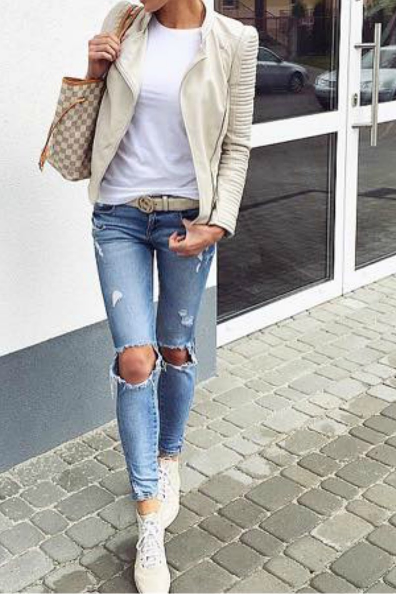 a women wearing a fall outfit with a gucci bag a gucci belt ripped blue jeans white sneakers and a cream leather motorcycle jacket