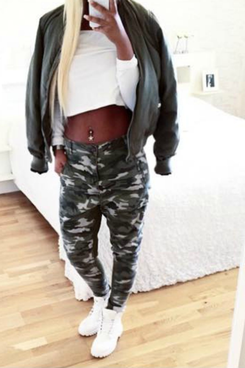 a girl taking a selfie in a mirror wearing A Tomboy Style Outfit with Camo Baggy Pants and White Sneakers and a Green Bomber Jacket
