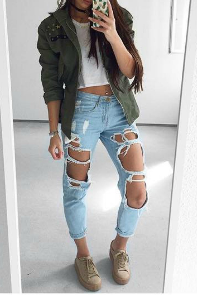 A young teen girl taking a selfie in a full length mirror wearing camel puma sneakers light blue ripped jeans a white crop top and a green military jacket with a black choker