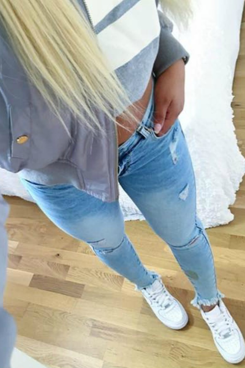 a blond teen girl taking a selfie in a mirror with light blue jeans and a bomber jacket